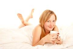 Café de consumición de la mujer joven en cama Fotografía de archivo libre de regalías