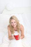 Café de consumición de la mujer joven en cama Fotografía de archivo