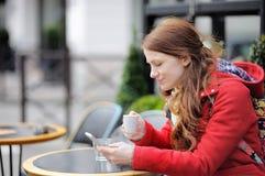 Café de consumición de la mujer joven y usar su teléfono elegante Imagenes de archivo
