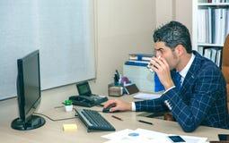 Café de consumición del hombre de negocios y trabajo con el ordenador Imagen de archivo libre de regalías