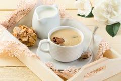 Café de la mañana con canela y leche en la bandeja de madera Foto de archivo