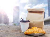 Café et croissant avec le sac de papier pour le petit déjeuner Image stock