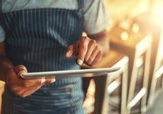 Caf?inhaber, der digitale Tablette verwendet stockfoto