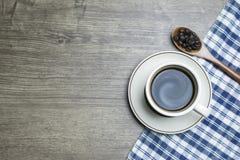 Caf? noir intense en tasse et grains de caf? r?tis par scoop en bois de cuill?re photo libre de droits