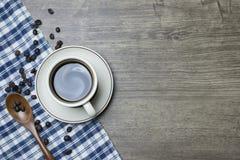 Caf? noir intense en tasse et grains de caf? r?tis par scoop en bois de cuill?re image stock