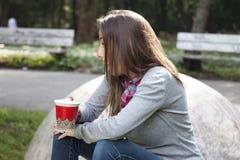 Café potable de belle jeune femme en parc de matin Photographie stock libre de droits