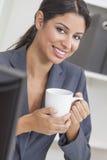 Café potable de femme d'affaires de femme dans le bureau Photo stock