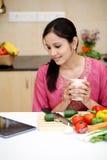 Café potable de femme dans sa cuisine Photographie stock libre de droits