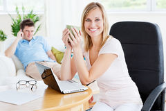 Café potable de femme gaie tout en à l'aide de l'ordinateur portatif Photo stock