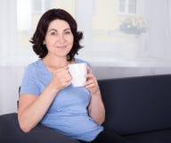 Café potable de femme mûr à la maison Image stock