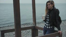 Café potable de jeune jolie femme mignonne sur le bord de mer de plage clips vidéos