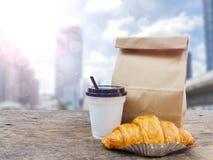 Café y cruasán con la bolsa de papel para el desayuno Imagen de archivo