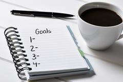Café y cuaderno con una lista en blanco de metas Imagen de archivo