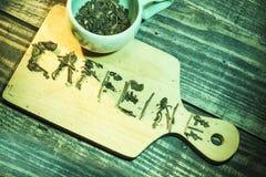 Cafeïnewoorden door groene theekruiden en kop thee worden voorgesteld op houten lijst die royalty-vrije stock afbeeldingen