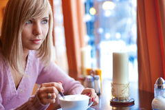 In cafe. Young beautiful woman is sitting in cafe with a white cup Royalty Free Stock Photo
