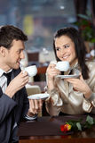 Cafe. Happy smiling couple in cafe with cups in hands Stock Image