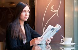 In a Cafe. Attractive brunette young woman reads a magazine sitting in a cafe, shallow DOF, focus on face Stock Image