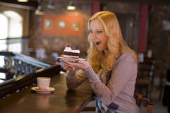 In cafe. The charming girl drinks coffee with a cake in cafe Stock Images