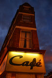 Cafe. A glowing cafe sign on a very narrow building in Balham, England royalty free stock images