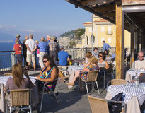 Cafe, Amalfi Coast, Italy. People eat, drink, and gather at a cafe on a cliff overlooking the Bay of Naples, on the Amalfi coast, near Sorrento in San Agnello Royalty Free Stock Photos