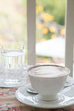 Cafe art latte coffee in the vintage cup on the tabel with a gla. Ss of water on the table Royalty Free Stock Image