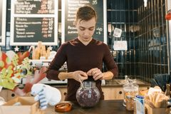 Cafe bar counter, young male barista preparing red natural herbal tea from rose petals hibiscus stock image