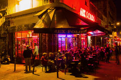 Cafe bar in the Parisian district Belleville at night. Paris, France - October 17, 2016: cafe bar in Belleville with unidentified people at night. Belleville is Royalty Free Stock Photography