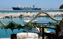 Ferryboat of Kefalonian lines. POROS PORT, KEFALONIA ,GREECE- AUGUST 2014 : Table and chair of terrace cafe bar with view the Poro's port and a ferryboat of Stock Photo