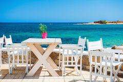 Cafe on the beach. Malia, Crete island, Greece. Beautiful tropical beach with turquoise water Royalty Free Stock Photo