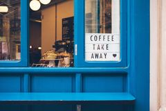 Cafe with blue color window and billboard. Is offering to buy take away cups of delicious coffee and food Stock Image