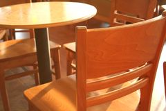 Cafe chair. Interior abstract of a cozy coffehouse. The shallow DOF is focused on the edge of the chair Stock Photos