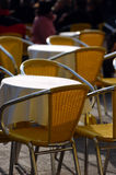 Cafe chairs and table. Yellow cafe chairs outdoors in a sunny day with table and some people in background Royalty Free Stock Photography