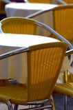 Cafe chairs and table. Yellow cafe chairs outdoors in a sunny day with table Stock Photos