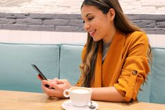 Free Cafe City Lifestyle Girl With Phone Drinking Cappuccino Texting Text On Smartphone App Sitting Indoor In Trendy Urban Cafe Stock Photos - 172650383