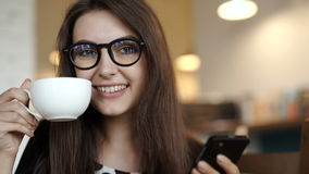 Cafe city lifestyle woman drinking coffee. Cafe city lifestyle woman on phone drinking coffee texting text message on smartphone app sitting indoor in trendy stock video