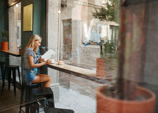Cafe city lifestyle woman sitting in trendy urban cafe reading m. Agazine and drinking coffee with a croissant during your vacation stock image