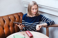 Cafe city lifestyle woman on tablet looks at the clock sitting indoor in trendy urban cafe. Stock Image