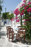 Cafe classic table chairs greek islands. Classic greek taverna furniture restaurant cafe on the stone painted street greece islands with flowers Stock Photography