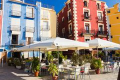 Cafe, colorful houses and palms on the street in Villajoyosa, Spain on a sunny day.  royalty free stock photography