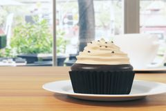 Cafe concept. Close up of chocolate cupcake with frosting and coffee cup on wooden table. Blurry background. Cafe concept. 3D Rendering Stock Images