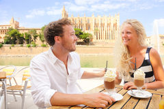Cafe couple dating drinking coffee cappuccino. On cafe talking on travel on Mallorca in front of La Seu, Palma Cathedral. Young couple on Majorca vacation stock image