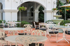 Cafe in courtyard of The Raffles Hotel, Singapore. White tables and chairs, cafe in courtyard of The Raffles Hotel, the famous hotel in Singapore Royalty Free Stock Photo