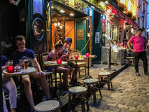 Cafe diners read and chat at Montmartre cafe on a summer evening Royalty Free Stock Photos