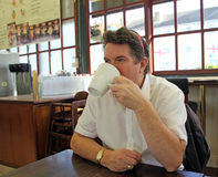 Cafe drinking coffee. Photo of a man in a seaside cafe drinking a delicious mug of cappuccino Royalty Free Stock Photos