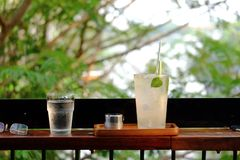 A glass of iced lemon soft drinks on wooden bench with green nature background. Cafe exterior area and sun light royalty free stock photos