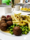 Cafe fried potatoes meatballs green peas stock images