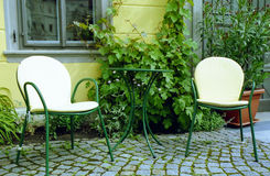Cafe furniture. Café furniture in front of a leaves-covered house Stock Images