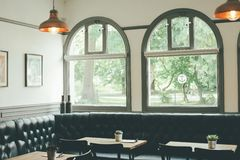 Cafe Interior With Black Corner Couch Glass Window Wooden Table and Pendant Lamps Stock Photography