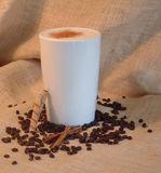 Cafe Latte. A giant mug of coffee (latte) sitting in the middle of scattered espresso beans with cinnamon sticks in front of a burlap background Royalty Free Stock Photos