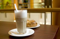 Cafe Latte. View of a glass of the trendy Cafe Latte and a cookie. The glass is in focus Stock Photography